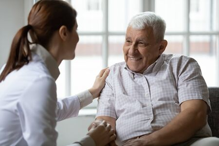 Caring nurse talks to old patient holds his hand sit in living room at homecare visit provide psychological support listen complains showing empathy encouraging. Geriatrics medicine caregiving concept