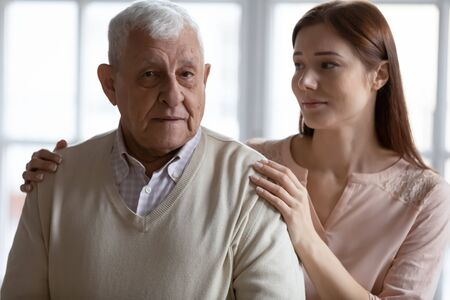Caring grown up granddaughter express sympathy stroking elderly grandfather related to senile disease memory loss, mental disorder or dementia. Caregiving older generation people nursing home concept Stockfoto
