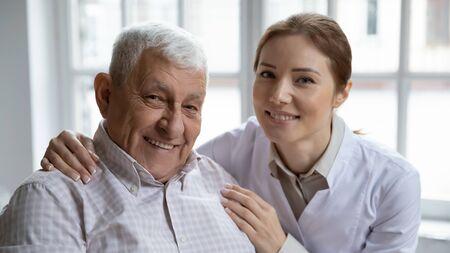Young nurse in white coat hugging old 80s man smiling looking at camera. Portrait of satisfied patient and his caregiver. Medical care of older generation people, geriatrics medicine, nursing concept Banco de Imagens