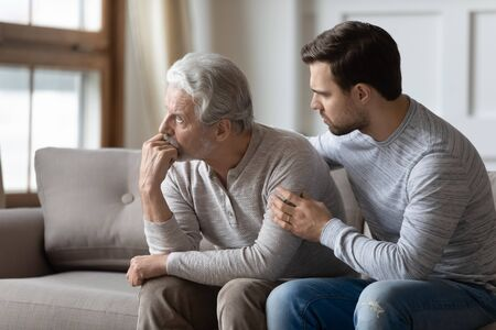Loving young man embrace comfort upset elderly gray-haired dad suffering from depression or problems, caring adult grown-up son hug caress support mature father feeling lonely distressed at home Foto de archivo
