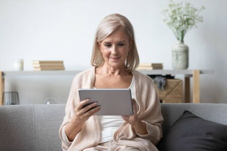 Portrait of pleasant middle aged woman sitting on cozy sofa, using tablet computer at home. Happy female retiree web surfing information, shopping in popular online store, reading electronic book. Imagens