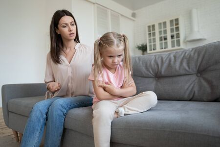 Sad stubborn little girl sit on couch back to mom feel offended avoid talking or listening, angry hurt small preschooler daughter ignore mother speak lecturing or scolding, family fight concept