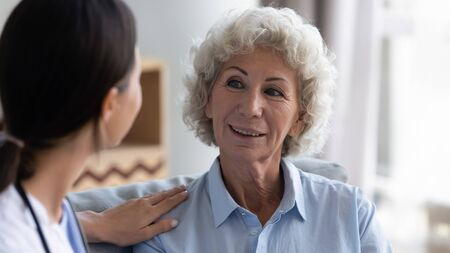 Attentive female caregiver visit positive senior old lady talking to retired lonely woman at home, caring doctor give help support consult mature grandmother, elderly healthcare concept