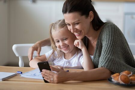 Happy mum and little daughter make self-portrait picture use cellphone together, smiling young mother and sweet small girl child look at camera taking posing for selfie, have video call on smartphone
