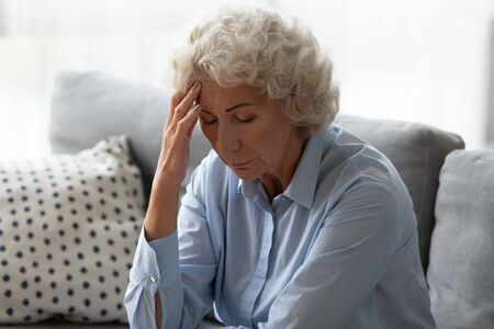 Sick senior woman sit on sofa at home feel distressed suffer from migraine or headache, ill mature female rest on couch touch head have dizziness from high blood pressure, elderly healthcare concept Imagens