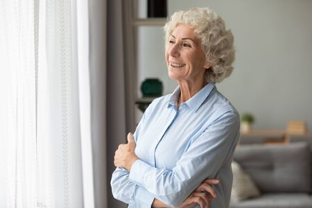 Happy elderly woman look in the window distance at home feel overjoyed excited about future, smiling mature female senior retired grandmother wait hope for the best to come, optimism concept Фото со стока
