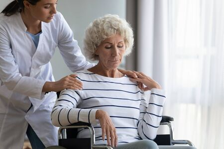 Caring young female nurse give help assist sad handicapped old lady in wheelchair, supportive caregiver take care of disabled mature grandmother in retirement house, elderly healthcare concept Reklamní fotografie