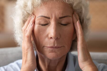 Close up of mature woman massage temples suffer from strong migraine or headache at home, sick old female struggle with blurry vision have high blood pressure, elderly healthcare concept