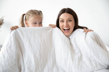 Portrait of overjoyed young mother and cute preschooler daughter hide behind blanket playing together in bedroom, smiling mom and little girl child have fun in bed look at camera posing