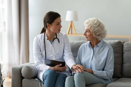 Supportive young woman doctor or nurse visit senior grandma patient at home talk consult, attentive female caregiver give help to elderly mature grandmother, old people healthcare concept