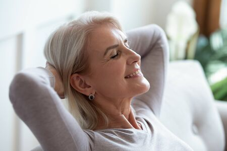 Smiling older woman relaxing with hands behind head on cozy sofa at home, happy sincere mature female with grey hair enjoying weekend, stretching on couch, resting and daydreaming, leaning back Archivio Fotografico