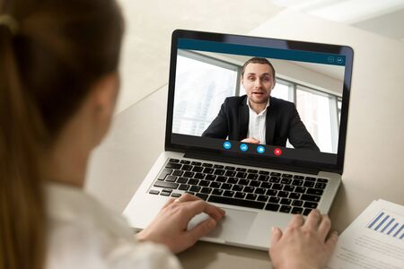 Back view of female employee talk with male businessman on webcam laptop conference, woman worker negotiate with man employer brainstorm on video call from home, online consultation concept
