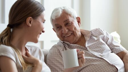 Close up smiling older father and adult daughter chatting, drinking tea or coffee, sitting on cozy couch at home, positive mature grandfather and young woman having fun, talking, sharing news