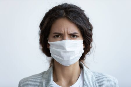 Close up headshot portrait of woman in protective medical mask from coronavirus feel anxious about pandemic, angry worried female wear face cover protecting from covid-19 corona epidemic