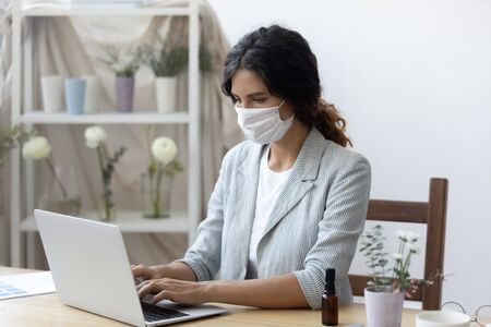 Young woman wear medical protective mask from corona virus pandemic work on laptop in office, female employee in face cover against covid-19 coronavirus epidemic use computer at workplace