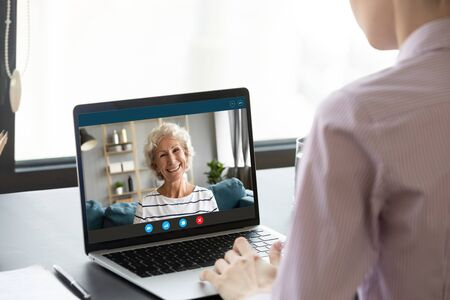 Focus on computer screen happy attractive middle aged mature hoary lady talking via video call with grown up daughter, working in office. Happy two generations family communicate talk speak online. 版權商用圖片