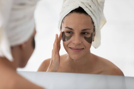 Close up face of woman reflected in mirror after morning shower she applied eyes hydrogel patches to reduce puffiness remove dark circles. Helpful beauty treatment, personal care and hygiene concept
