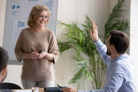 Confident male employee raise hand ask answer question at presentation or training in office, active man worker volunteer interact with female coach or presenter at briefing, cooperation concept