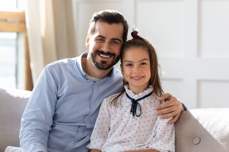Head shot portrait young handsome bearded man cuddling little school aged kid daughter, sitting together on sofa. Pleasant father hugging small child girl, looking at camera, posing for family photo.