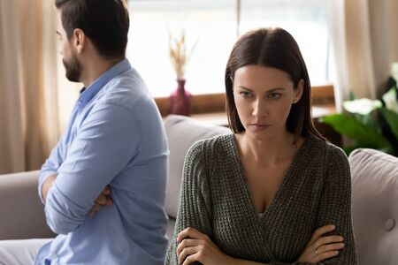 Focus on frustrated frowning young woman sitting separately from upset husband boyfriend on sofa after clarifying relationships at home. Stressed depressed couple ignoring each other after quarrel.