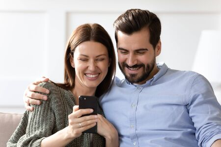 Head shot close up laughing young woman sitting on couch with joyful boyfriend husband, looking at smartphone screen. Happy married family couple watching funny video, making selfie on mobile.