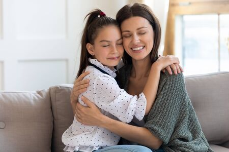 Affectionate young daughter touching heads with loving mommy, enjoying sweet tender moment in living room. Happy two female generations family cuddling, sitting with closed eyes on cozy couch. Stock Photo
