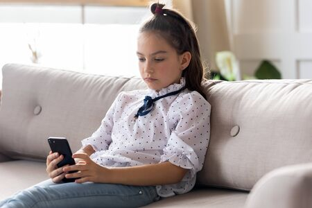 Serious little schoolgirl sitting on sofa, using smartphone mobile apps alone at home. Focused small child girl looking at cellphone screen, playing online game, web surfing internet in living room.