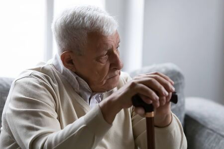 Serious gray-haired man hold wooden walking stick sit on couch in living room alone look at distance feels upset and lonely. Nursing home for older disabled people, senile diseases, healthcare concept
