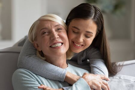 Happy elderly mother and grown-up daughter relax at home hugging and cuddling, smiling mature mom and adult millennial girl child embrace enjoy close tender family time together, bonding concept