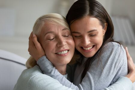 Happy mature mother and adult daughter hug cuddle share tender close moment at home together, smiling elderly mom and grown-up millennial girl child embrace show love and care, bonding concept