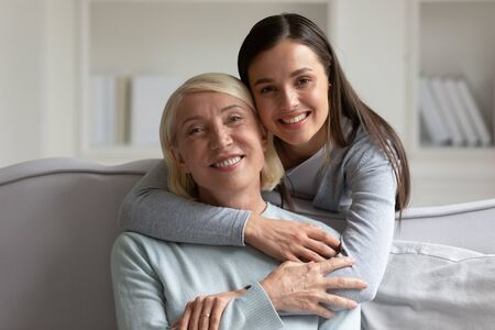 Portrait of smiling millennial girl hugging happy mature mother relaxing together in living room, overjoyed elderly mom and grown-up adult daughter embrace enjoy leisure domestic weekend at home