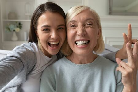 Smiling millennial girl child take selfie with overjoyed funny elderly mother at home, happy grown-up adult daughter have fun make self-portrait picture with mature mom, relax together on weekend
