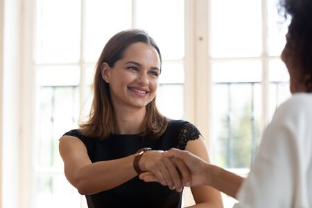 Multi-ethnic women broker and customer shake hands. Caucasian hr manager greets african applicant ending successful job interview, good first impression, make deal, business etiquette gesture concept
