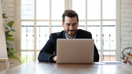 Millennial businessman in glasses formal suit sitting at desk in modern board room working using wireless computer business application, search information, interaction on-line communication concept 写真素材