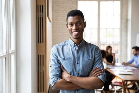 Millennial african ethnicity staff member with arms crossed feels confident posing in modern office boardroom looking at camera. Hired happy employee, executive manager portrait, company boss concept