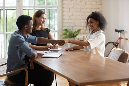 Businesspeople gathered in office start group business meeting greeting each other shake hands express respect. Accomplishment of successful job interview, bank workers and client closing deal concept 写真素材