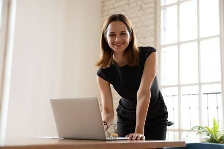 Confident female executive manager leaning over desk was distracted from working typing on laptop smiling looking at camera. Portrait of successful businesswoman, hired employee company representative 写真素材
