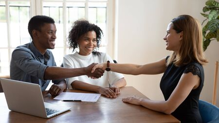 Happy smiling African married couple shake hands to mortgage insurance woman broker. Formal meeting with financial advisor, real estate agent, consulting, make deal, handshake gesture of trust concept