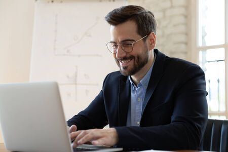 Smiling businessman in glasses and formal suit typing on laptop seated at modern boardroom. Informal chat personal correspondence, received good news, read offer e-mail, work in office process concept