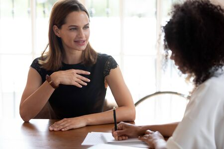 Job interview hiring process concept. African HR manager interviewing applicant to company vacancy, multi-ethnic women talking sitting at office desk. Advisor insurance broker and client communication