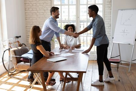 Multi-ethnic business people gather in boardroom start meeting caucasian boss african client shake hands showing respect. Closing deal, successful negotiations ending, acquaintance of parties concept