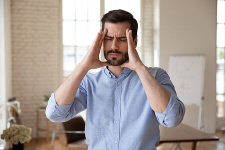 Millennial businessman standing in office touches head closed eyes feels unhealthy suffers from throbbing headache, concept of overloaded worker, stressful job, problems crisis, need treatment concept