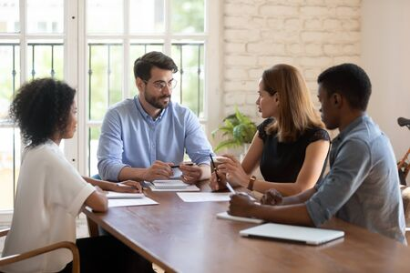 Four diverse business partners negotiating in boardroom. Businesspeople talking solving issues together, workgroup working on common project, share solutions, meeting lead by caucasian female leader 写真素材
