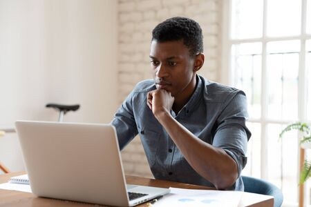 Concentrated serious african ethnicity worker sit in front of laptop reading e-mail feels concerned. Got unpleasant news, search of problem solution, thinking over challenge, fruitful workday concept