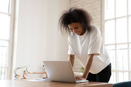 Happy mixed-race businesswoman leaning over desk chatting on-line ending workday enjoy distant informal communication. Office worker working typing on laptop read positive e-mail, send message concept 写真素材