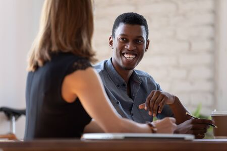 African manager listen to client preferences at business meeting, diverse teammates working together, mentor and intern talk. Job interview good first impression positive pleasant conversation concept