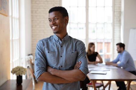 Confident African corporate member standing with arms crossed in modern boardroom smiling looks away daydreaming mates on background. Successful businessman, hr manager, company owner portrait concept 写真素材