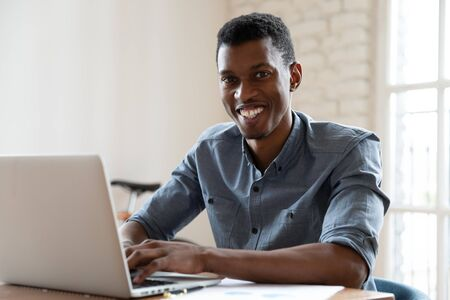 African ethnicity office worker looking at camera smiling while working at computer indoors. Concept of leadership, successful entrepreneur, happy manager, salesman broker or financial advisor concept