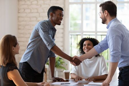 Before start negotiations African and Caucasian businessmen partners greets each other shake hands express respect friendly attitude. Closing deal, reach agreement, congratulate to promoted employee