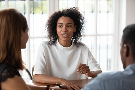 Mixed race African female applicant passing job interview answers on questions sitting opposite multi-ethnic HR managers during meeting in office. Human resources, staffing, hiring, recruiting concept